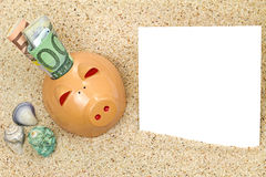 Piggy bank with rolled money on beach sand Stock Image