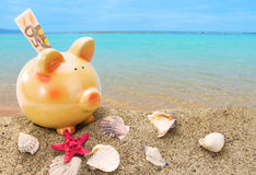 Piggy bank on sand with sea Royalty Free Stock Photography