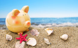 Piggy bank on sand with sea Stock Images