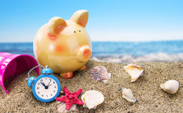 Piggy bank on sand with sea. Piggy bank on sand with summer sea background Royalty Free Stock Image