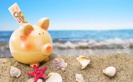 Piggy bank on sand with sea. Piggy bank on sand with summer sea background Royalty Free Stock Photography