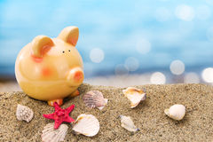 Piggy bank on sand with summer sea Royalty Free Stock Image