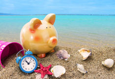 Piggy bank on sand with summer sea. Background Stock Photos