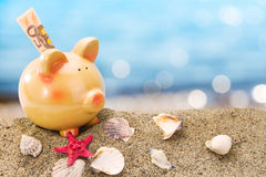 Piggy bank on sand with summer sea Stock Photos