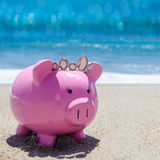 Piggy bank on the sandy beach Royalty Free Stock Photos