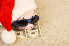 Piggy bank with Santa Claus hat standing on towel from greenback hundred dollars with sunglasses on the beach sand. Horizontal stock image