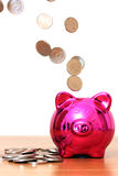 Piggy bank savings. Pink piggy bank with money pouring into it royalty free stock photography