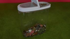 Piggy bank, savings box. Piggy bank for coins against a green background stock footage
