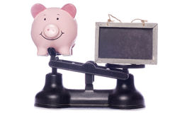 Piggy bank on scales with blackboard Stock Photos