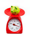Piggy bank on the scales. The smile green piggy bank on the scales white background Royalty Free Stock Photos