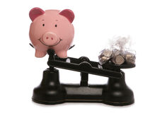 Piggy bank on scales with sterling money Stock Photos