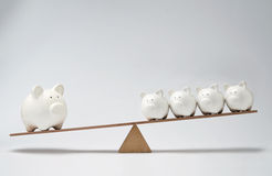 Piggy bank seesaw. Small piggy banks and large piggy bank balancing on a seesaw Stock Image