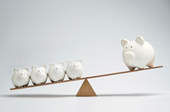 Piggy bank seesaw. Small piggy banks and large piggy bank balancing on a seesaw Royalty Free Stock Photography