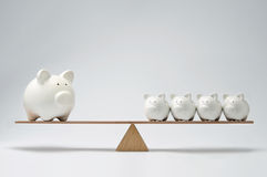 Piggy bank seesaw. Small piggy banks and large piggy bank balancing on a seesaw Stock Images