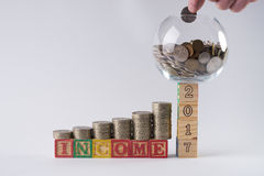 Piggy bank set on wooden blocks number 2017 with Businessman`s hand putting coin in money jar Stock Photo
