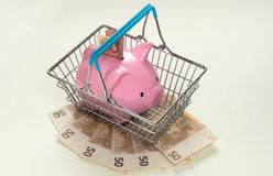 Piggy bank in shopping basket with many euros Royalty Free Stock Images