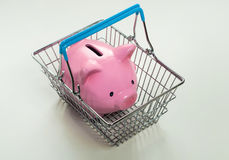 Piggy bank in shopping basket Royalty Free Stock Images