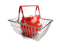 Piggy bank in shopping basket on white background Royalty Free Stock Images