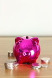 Piggy bank with silver coins. Pink piggy bank with piles of silver coins arround it stock image