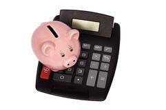 Piggy Bank Sitting On Top Of Calculator. Overhead shot of piggy bank setting on top of calculator.  Isolated on white Royalty Free Stock Images