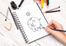 Piggy bank sketch on paper. Stock Image