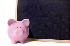 Piggy bank with small blank blackboard, isolated on white background, school fees saving concept Royalty Free Stock Image