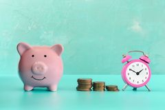 Between the piggy bank and a small pink alarm clock, three stacks of coins are in order. The symbol of the growth of. Money in time. Beautiful business still Royalty Free Stock Photos