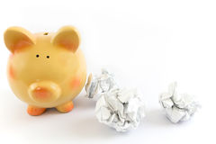 Piggy bank with some crumpled paper balls Royalty Free Stock Photos