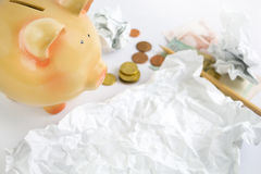 Piggy bank with some crumpled paper and money Royalty Free Stock Images