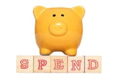 Piggy bank with spend alphabet blocks. Studio cutout Stock Photography