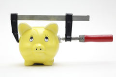 Piggy bank squeezed in a clamp Stock Photos