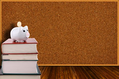 Piggy Bank on Stack of Books and Corkboard Background Royalty Free Stock Images