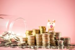 A piggy bank stacking on coins pile with jar glass for saving money or business planning concept stock photography