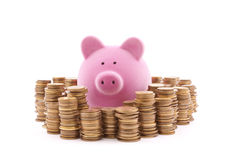 Piggy bank with stacks of coins. Royalty Free Stock Images