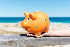 Piggy bank standing by the beach. Woman´s hand holding piggy bank by the beach Stock Photo