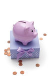Piggy bank standing on a gift box,. Pretty pggy Bank stands on a gift box with bow,  on white background Royalty Free Stock Photos