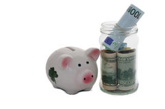 Piggy bank standing on money dollars and euros Stock Photography