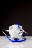 Piggy bank with a stethoscope Stock Photos