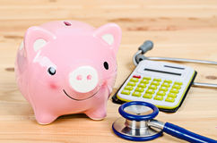 Piggy bank and stethoscope with calculator. Piggy bank and stethoscope with calculator on wooden background Royalty Free Stock Photos