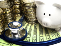 Piggy Bank With Stethoscope, Gold Coins And Money. Piggy bank and stethoscope with gold coins and money. Indicates wealth, money, strong finances, savings Stock Photography