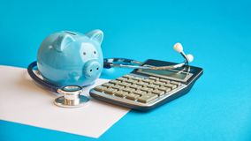 Piggy bank with stethoscope  on blue background. concept of financial literacy. Creating and maintaining a
