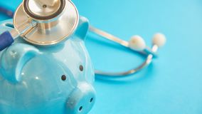 Piggy bank with stethoscope  on blue background. concept of financial literacy. Creating and maintaining a. An Image of a piggy and a stethoscope stock photography