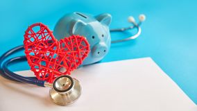 Piggy bank with stethoscope  on blue background. tax offset concept. Medical Expense Deductions and Tax Breaks