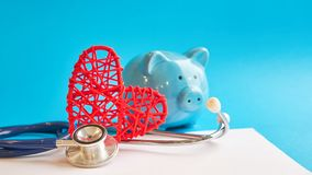 Piggy bank with stethoscope isolated on blue background. tax offset concept. Medical Expense Deductions and Tax Breaks