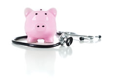 Piggy Bank and Stethoscope Isolated on White. Piggy Bank and Stethoscope Isolated on a White Background Royalty Free Stock Photography