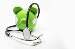 Piggy bank and stethoscope. Isolated on white background Royalty Free Stock Photo