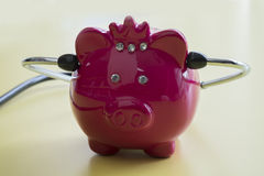 Piggy bank with stethoscope isolated. On white, concept for financial checkup or saving Stock Photography