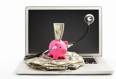 Piggy bank with stethoscope on laptop Royalty Free Stock Images