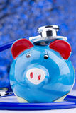 Piggy bank with a stethoscope: medical expenses Royalty Free Stock Photo