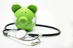 Piggy bank and stethoscope Stock Images